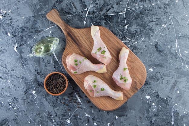 Pilons de poulet sur une planche à découper à côté de bols d'huile et d'épices, sur la surface bleue.