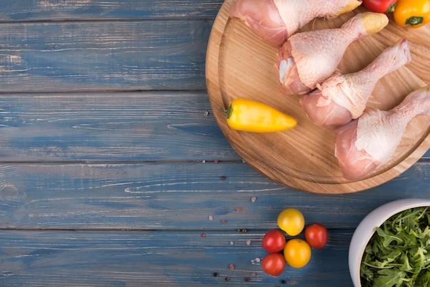 Pilons de poulet à plat sur planche de bois et ingrédients avec espace copie