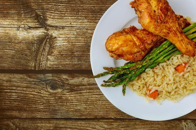 Pilons de poulet rôti avec riz sur table en bois rustique. vue de dessus.