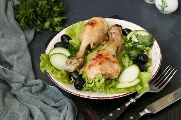 Pilons de poulet servis avec concombres, olives noires et laitue sur assiette