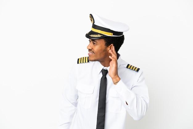 Pilote d'avion afro-américain sur fond blanc isolé écoutant quelque chose en mettant la main sur l'oreille