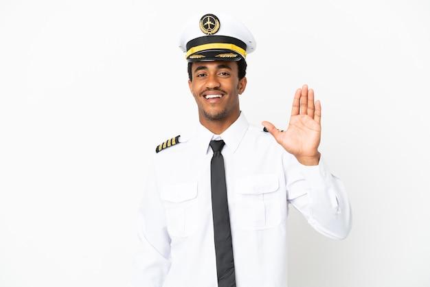 Pilote d'avion afro-américain sur fond blanc isolé saluant avec la main avec une expression heureuse