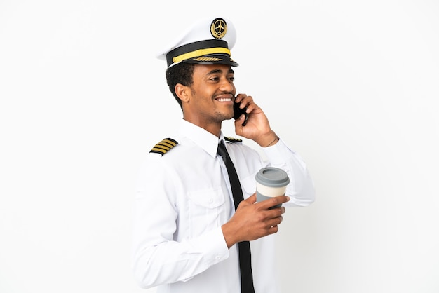 Pilote d'avion afro-américain sur fond blanc isolé tenant du café à emporter et un mobile