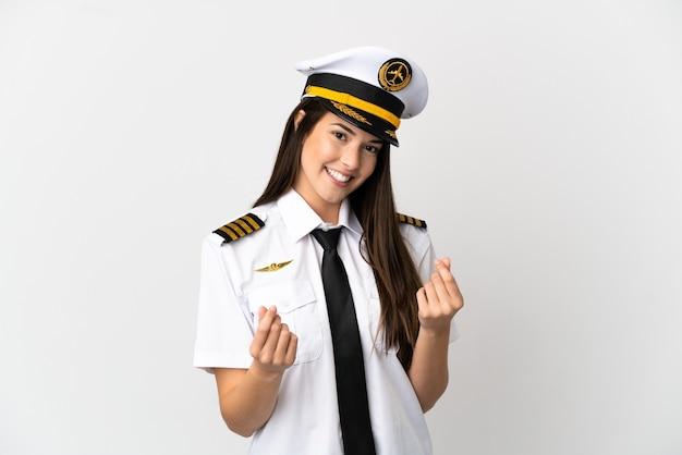 Pilote d'avion fille brésilienne sur fond blanc isolé faisant le geste de l'argent