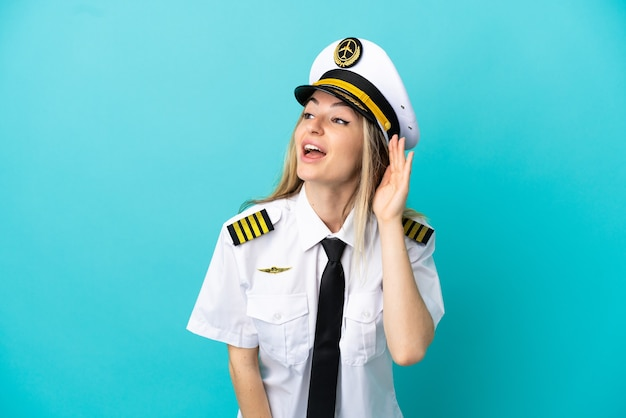 Pilote d'avion sur fond bleu isolé écoutant quelque chose en mettant la main sur l'oreille
