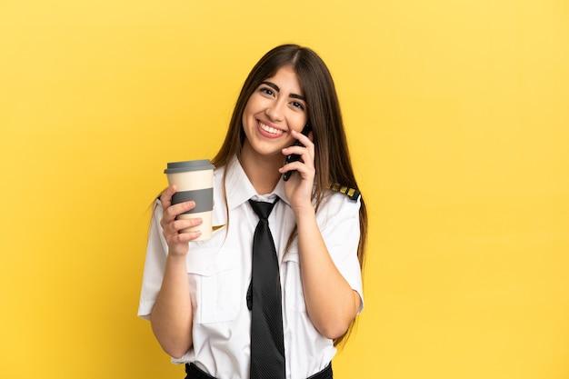 Pilote d'avion isolé sur un mur jaune tenant du café à emporter et un mobile