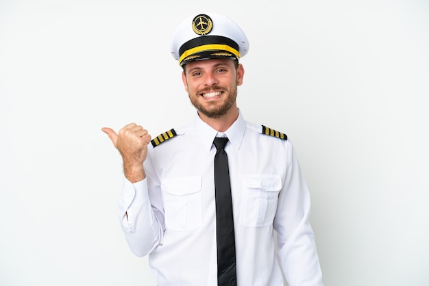 Pilote brésilien d'avion isolé sur fond blanc pointant vers le côté pour présenter un produit