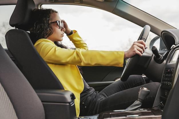 Pilote brune à lunettes de soleil, veste jaune regarde par la fenêtre de sa voiture.