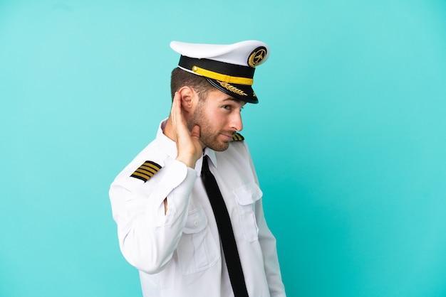 Pilote caucasien d'avion isolé sur fond bleu écoutant quelque chose en mettant la main sur l'oreille
