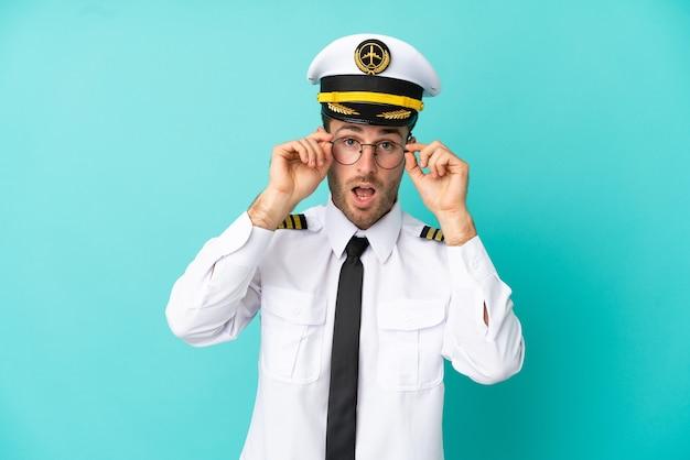 Pilote caucasien d'avion isolé sur fond bleu avec des lunettes et surpris