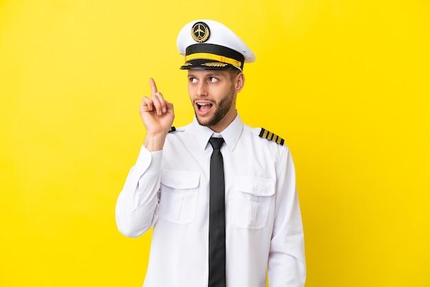 Pilote caucasien d'avion isolé sur fond jaune dans l'intention de réaliser la solution tout en levant un doigt vers le haut