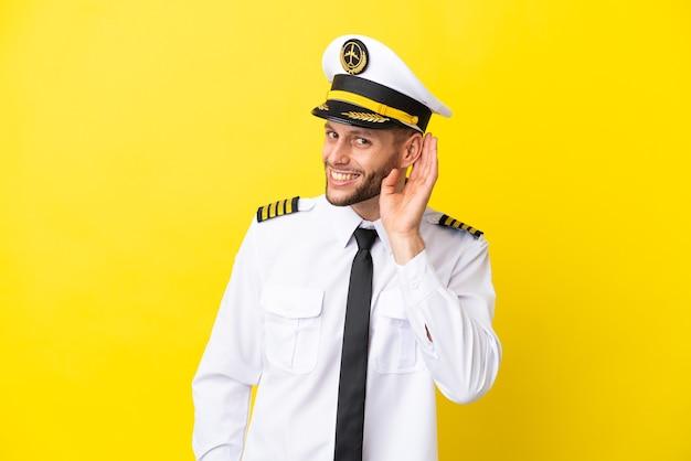 Pilote caucasien d'avion isolé sur fond jaune écoutant quelque chose en mettant la main sur l'oreille