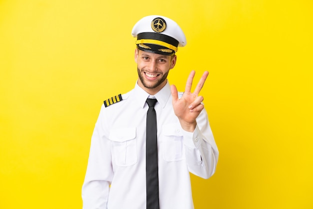Pilote caucasien d'avion isolé sur fond jaune heureux et comptant trois avec les doigts