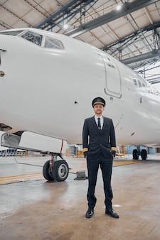 Le pilote confiant de profesol vérifie l'avion dans le hangar
