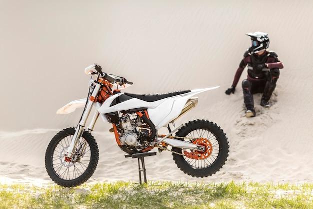Pilote élégant avec moto dans le désert