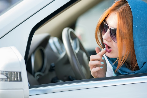 Pilote de femme d'affaires assez à la mode en écharpe et lunettes de soleil vérifiant son maquillage dans un miroir.