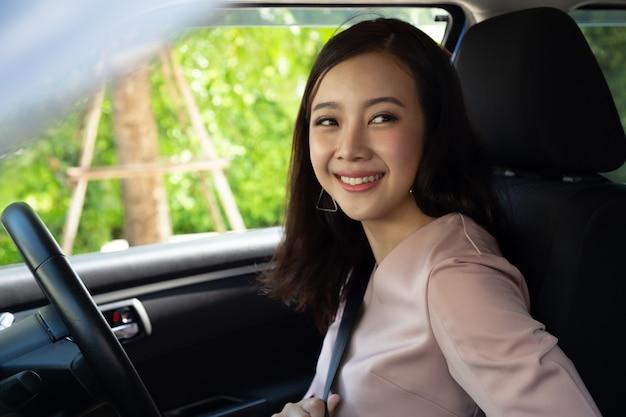 Pilote femme asiatique mettant la ceinture de sécurité à l'intérieur de la voiture