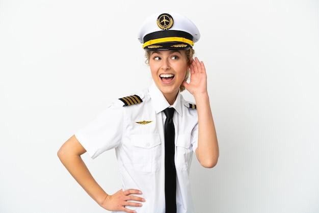 Pilote de femme blonde d'avion isolé sur fond blanc écoutant quelque chose en mettant la main sur l'oreille