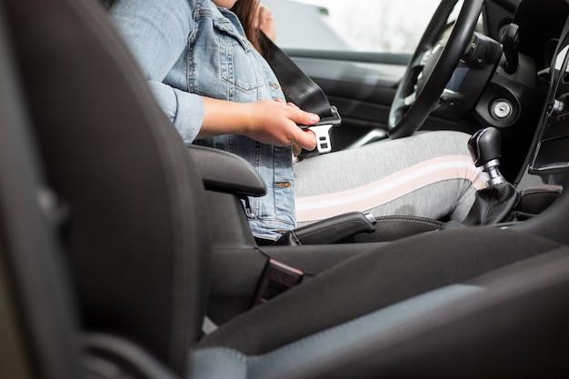 Pilote femme ceinture de sécurité de fixation dans la voiture, contre un accident de voiture, concept de sécurité, transport en toute sécurité