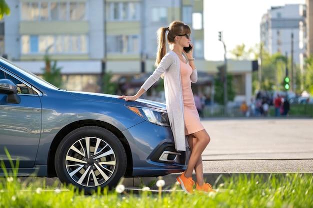 Pilote de femme élégante debout près de son véhicule parlant au téléphone portable dans la rue de la ville en été.