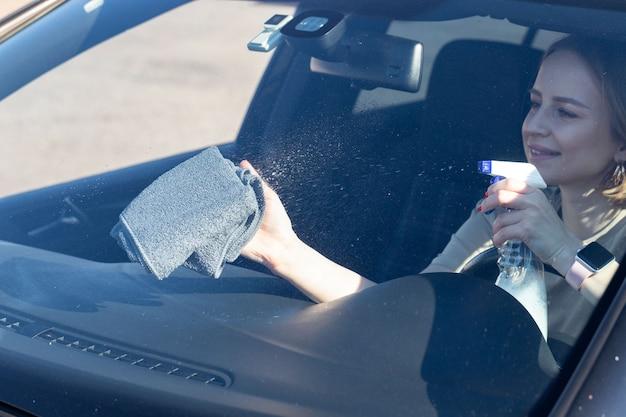 Pilote de femme nettoyant le pare-brise de voiture avec spray, essuie avec microfibre de la poussière et de la saleté.