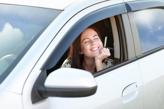 Pilote de fille heureuse regarde par la fenêtre de la voiture