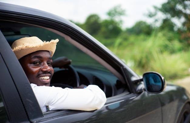 Pilote de l'homme africain souriant alors qu'il était assis dans une voiture
