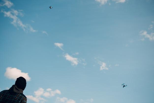 Pilote d'homme contrôlant deux drones quadcopter avec télécommande.
