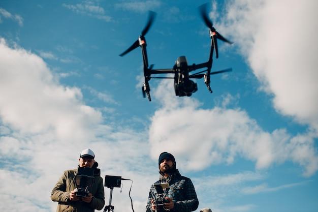 Pilote d'homme contrôlant un drone quadricoptère avec télécommande.
