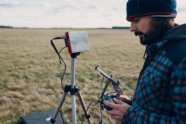 Pilote d'homme contrôlant un drone quadricoptère avec télécommande