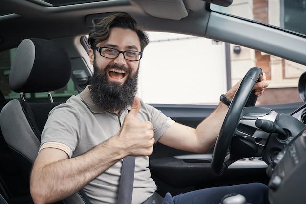 Pilote homme heureux souriant montrant les pouces vers le haut au volant de voiture de sport