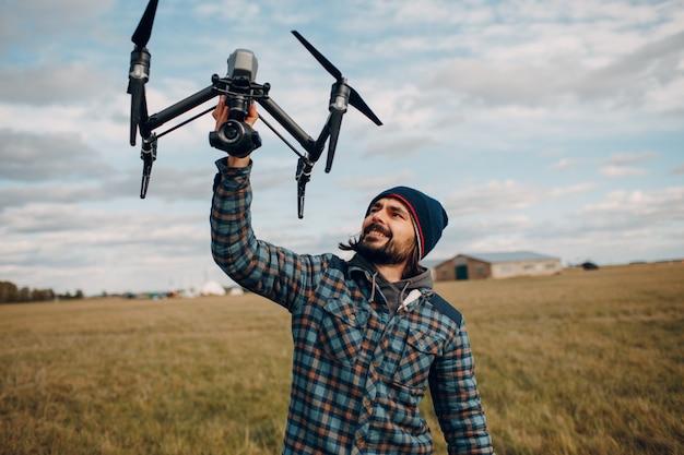 Pilote d'homme tenant un drone quadricoptère dans les mains à l'extérieur du champ.