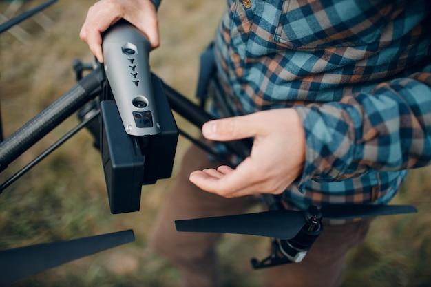 Pilote d'homme vérifiant le drone quadcopter avant le vol aérien et le tournage.
