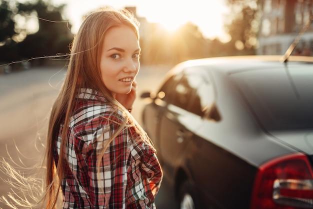 Pilote de jeune femme joyeuse posant contre une voiture