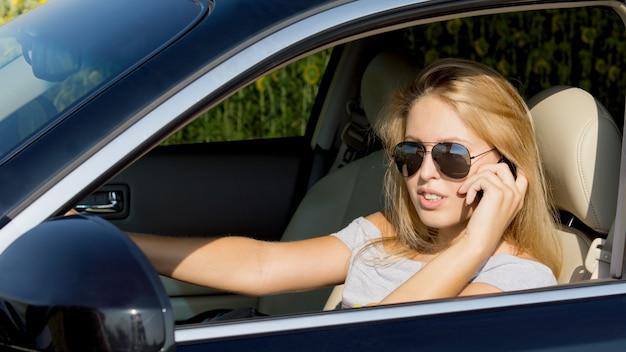 Pilote de jeune femme à lunettes de soleil parler sur son téléphone portable alors qu'il était assis dans le siège du conducteur d'une voiture à l'arrêt