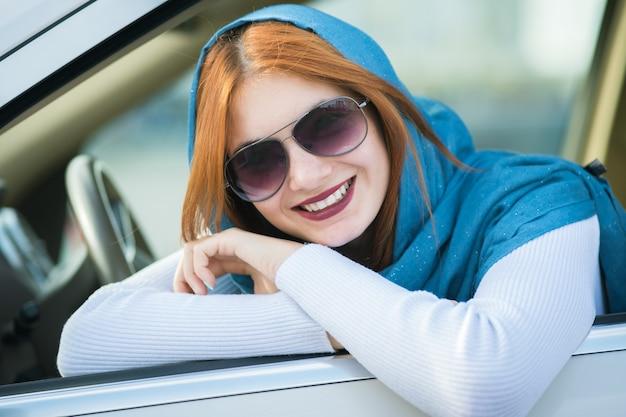 Pilote de la jeune femme à la mode en écharpe et lunettes de soleil en regardant par la fenêtre avant de la voiture.