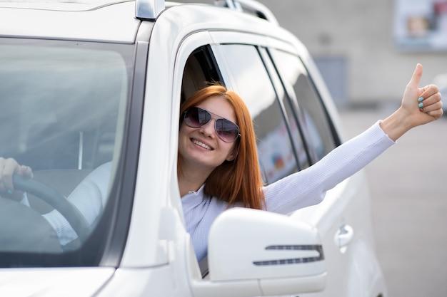 Pilote de jeune femme montrant les pouces vers le haut de geste derrière le volant de voiture.