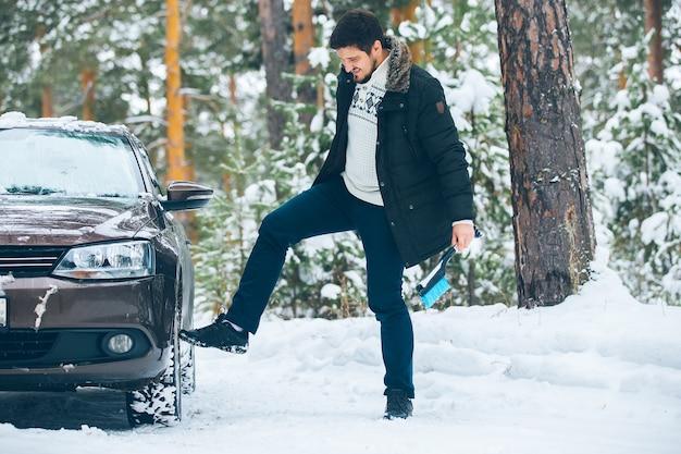 Un pilote maléfique donne un coup de pied au volant d'une voiture en hiver dans les bois