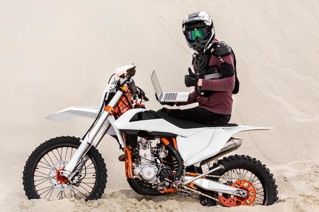 Pilote moto avec casque tenant un ordinateur portable