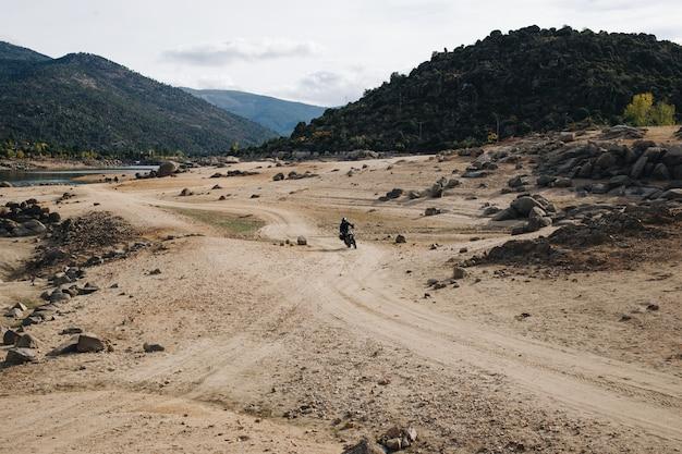 Pilote de moto sur piste de gravier tout-terrain