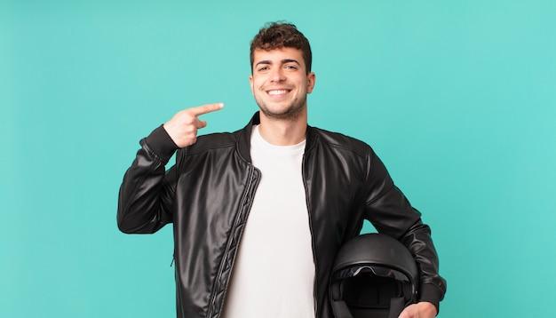 Pilote de moto souriant pointant avec confiance vers son propre large sourire, attitude positive, détendue et satisfaite