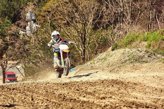 Pilote de motocross en action accélérant la moto décolle et saute sur le tremplin sur la piste de course.