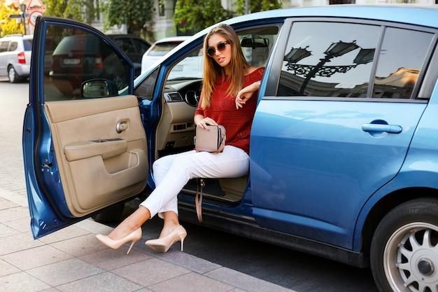 Pilote portant des talons et assis dans sa voiture moderne bleue.