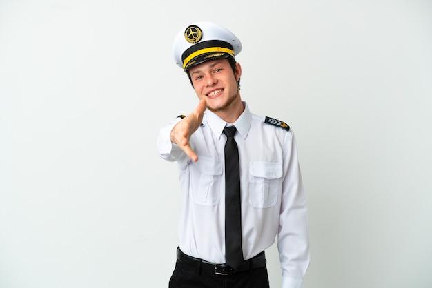 Pilote russe d'avion isolé sur fond blanc se serrant la main pour conclure une bonne affaire
