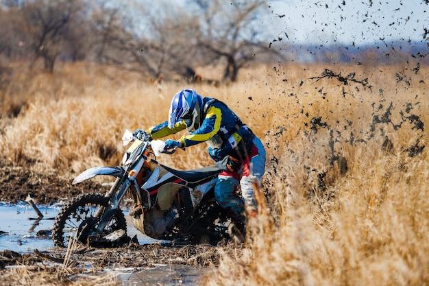 Pilote de vélo d'enduro coincé dans la boue profonde
