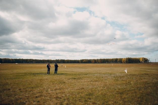 Pilotes d'hommes contrôlant un drone quadricoptère et un avion rc avec télécommande à l'extérieur de l'aéroport de terrain