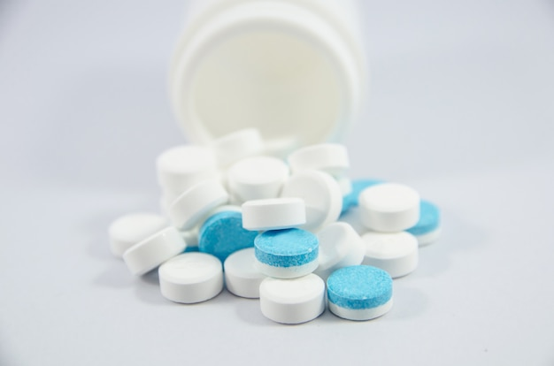 Pilule blanche et bleue sur fond noir blanc avec une bouteille