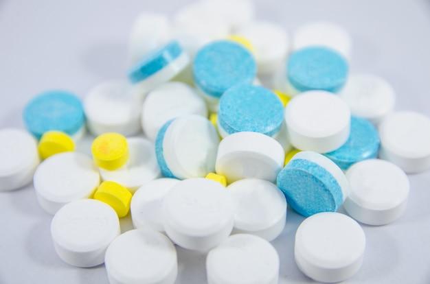Pilule blanche, bleue et jaune sur fond noir blanc