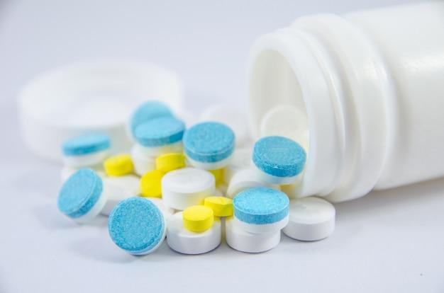 Pilule blanche, bleue et jaune sur fond noir avec bouteille