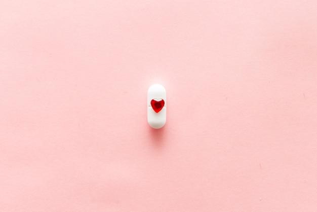 Une pilule blanche sur fond rose avec forme de coeur rouge, médicaments cardiaques ou concept de traitement féminin